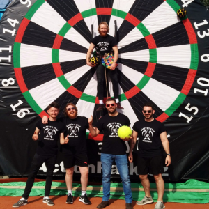 men in front of a gigantic dartboard